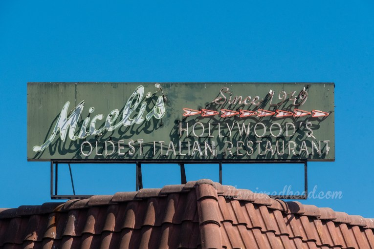 "A green neon sign sits on the roof reading ""Miceli's since 1949 Hollywood's Oldest Italian Restaurant"""