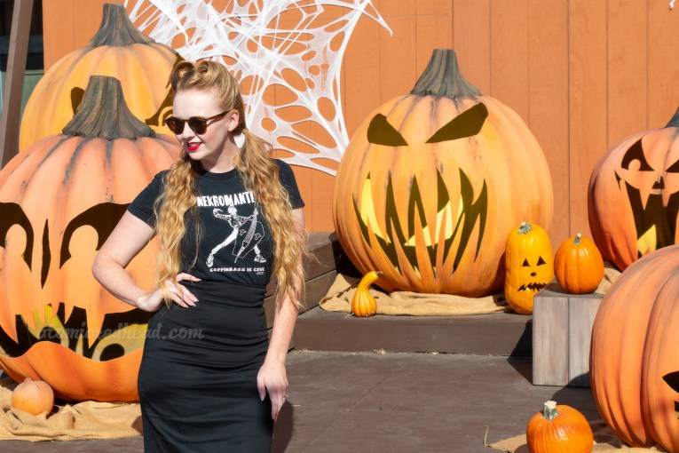 "Myself, wearing a black t-shirt with a zombie playing an upright bass shaped like a coffin, and text reading ""Nekromatix Coffinbass is Cool"" and a black pencil skirt, standing in front of a stage with massive jack o'lanterns."
