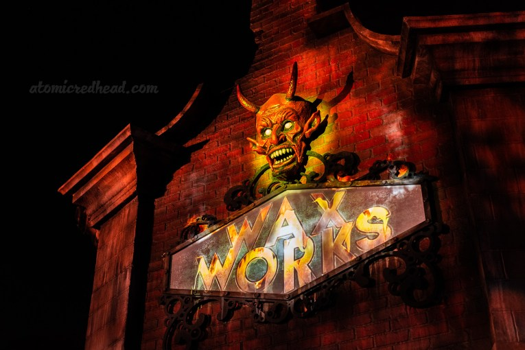 "The entrance to Wax Works, a brick building with a devil head above the sign reading ""Wax Works"""