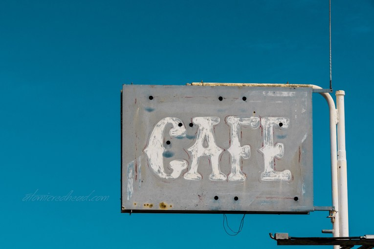 "A faded grey-blue sign reading ""Cafe"" in faded white letters."