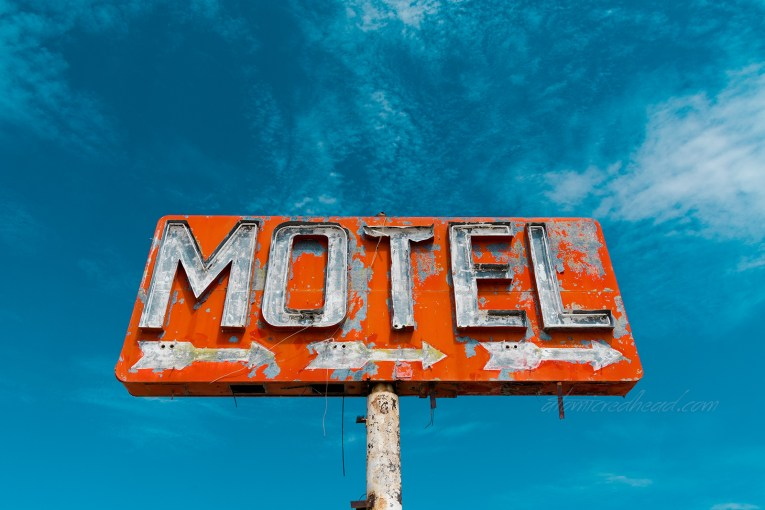 """A red sign with flaking paint reads """"Motel"""" in broken neon. Three small arrows point to the right."""