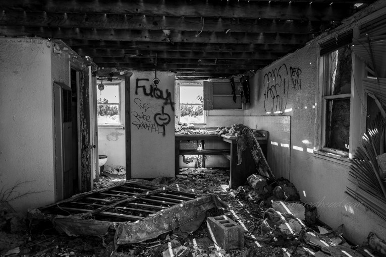 Inside the Twin Arrows Trading Post. A black and white photo of a ceiling stripped to its studs. An overturned mattress lays on the floor to the left. Insulation and other debris scatter the floor.