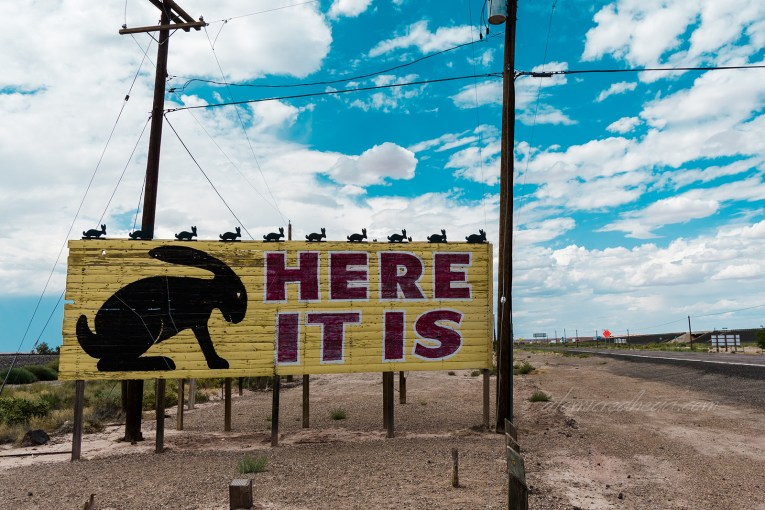 "A large, low billboard is yellow and features a large black jackrabbit, red letters to the right read ""HERE IT IS"" and small jackrabbits line the top of the billboard."