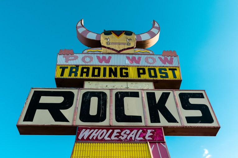 Sign for the Pow Wow Trading Post. A massive kachina doll sign made of plastic and metal stands tall against a blue sky.