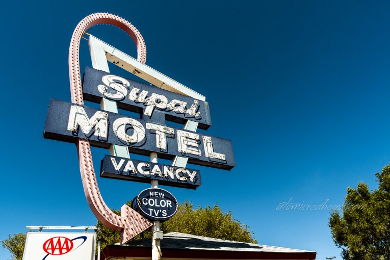 "Faded neon sign for the ""Supai Motel"" which is made up of blue square and a faded red curling arrow."