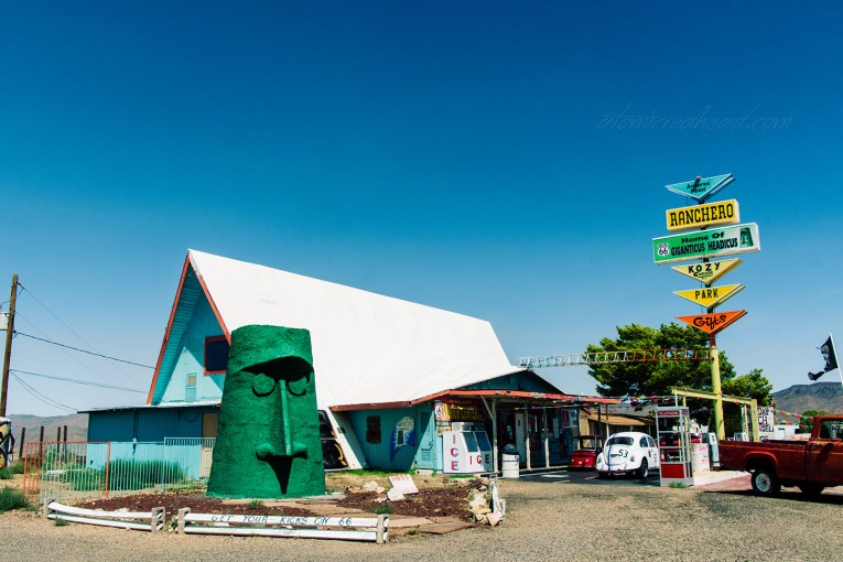 "A blue A-frame building sits with a white roof. A massive green tiki heads sits out front. A colorful sign reads ""Antares Point Ranchero Home of Giganticus Headicus"""