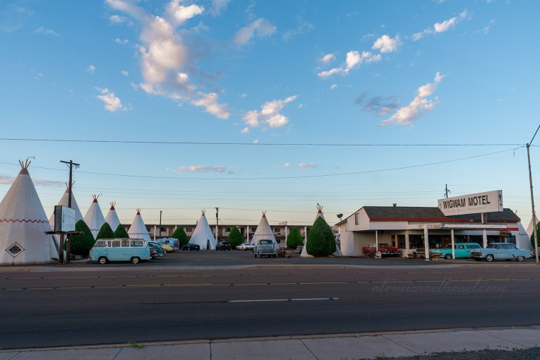 The Wigwam Village from across the street. A semi-circle of tipis around a flat roofed middle office in the middle. Classic cars are parked out front.
