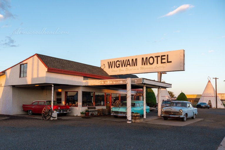 "The office for the Wigwam Motel, a flat roof building painted white and trimmed in red. Classic cars sit out front. Black text reads ""Wigwam Motel Have You Slept in a Wigwam Lately?"""