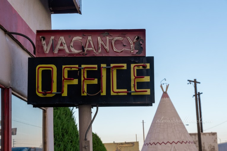 "A neon sign, the top portion is red and reads ""Vacancy"" in white neon, the lower part is black, with yellow letters spelling ""Office"" with red neon over the top."