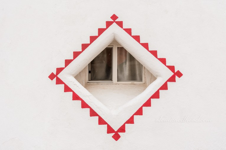 The window of the tipis, which is a diamond shape and painted in a geometric red design.