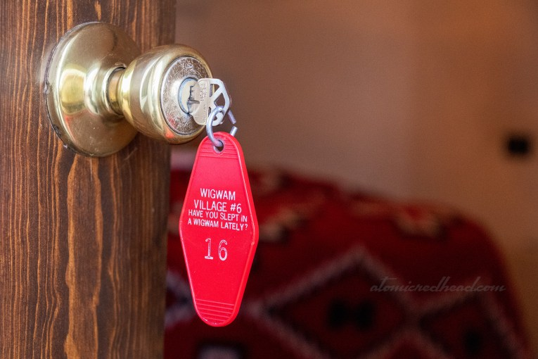 "Our key for room 16 is in the door, a red key fob reading ""Wigwam Village #6 Have You Slept In a Wigwam Lately 16"""