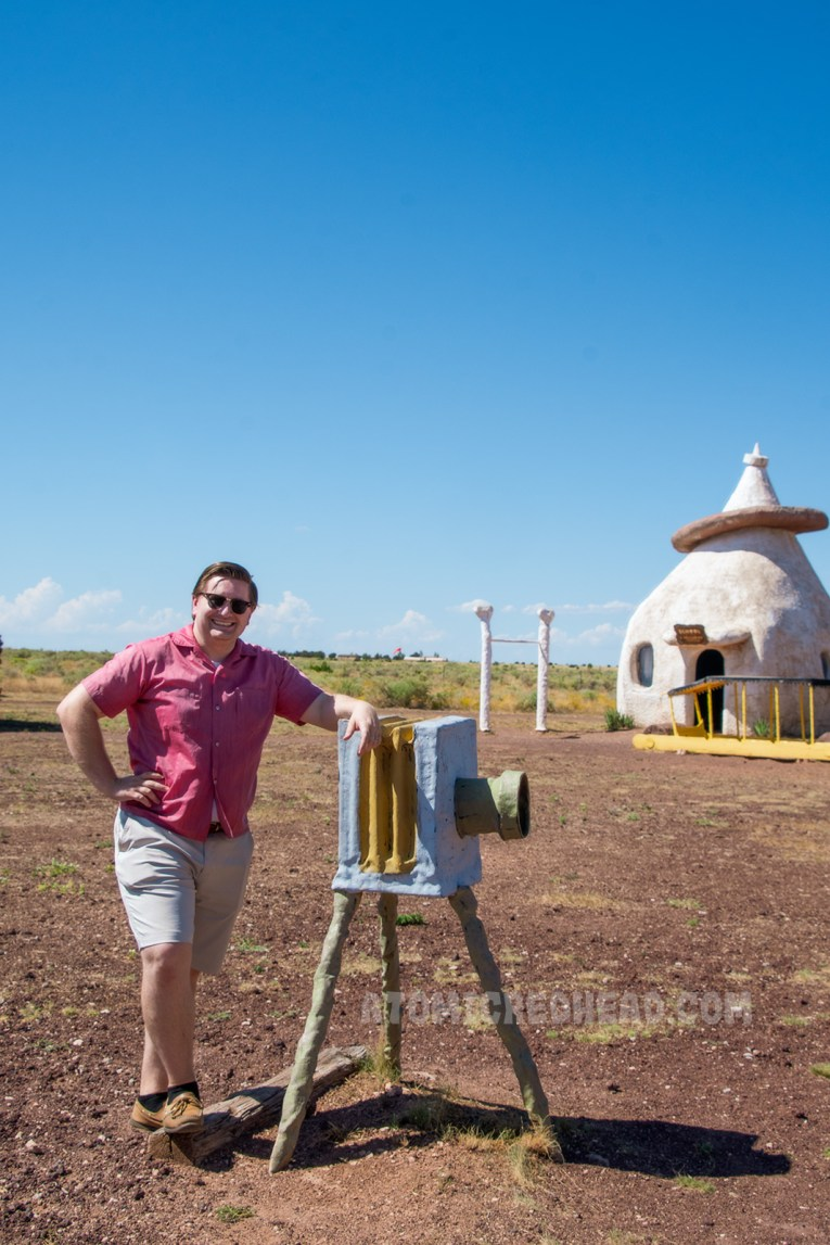 Pat, wearing a red button down shirt and tan shorts, poses next to the faux camera. Behind him an odd tapered building made of concrete stands, which is the school house.