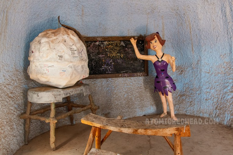 Inside the school house a blackboard is on the wall, and a statue of a cartoon school teacher in a purple cavewoman dress.