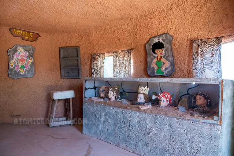 "Inside the Beauty Salon, a display case with heads featuring different ""stone age"" hairstyles using bones sit inside. On the wall paintings of various stone age beauties."