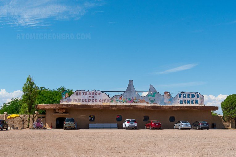 "The main building, a single store building with round windows and appears as if it were carved from a giant rock. A large sign atop reads ""Entrance to Bedrock City"""