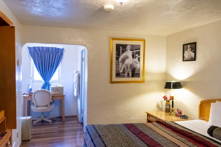Inside our room, a white room with images of Marilyn Monroe on the wall, an archway on the left opens to a small desk.