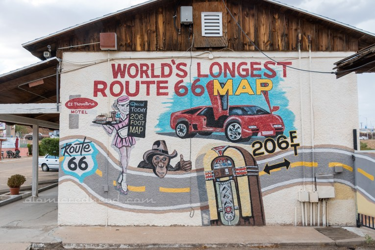 "A mural of a road, with a waitress in a 50s style pink uniform, a jukebox, and red sports car, with text reading ""World's Longest Route 66 Map"" painted above."