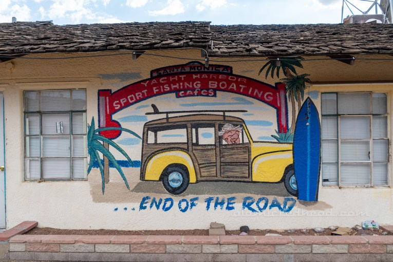 "Mural of a woody wagon sitting under the Santa Monica Pier sign, with text reading ""...end of the road"" at the bottom."