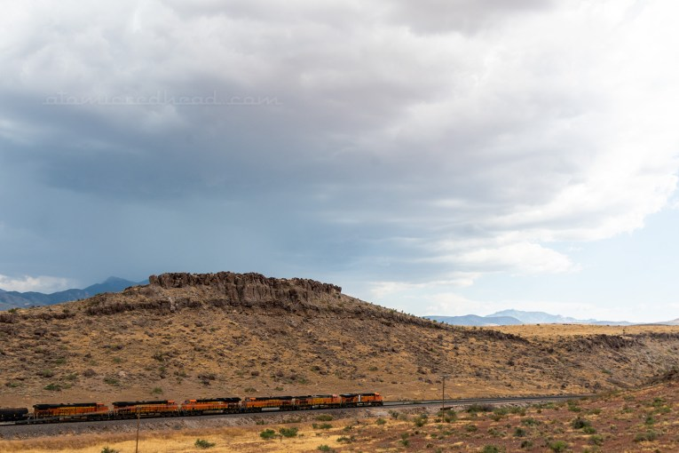 View of Slaughterhouse Canyon, with a mesa rising behind a train along the tracks.