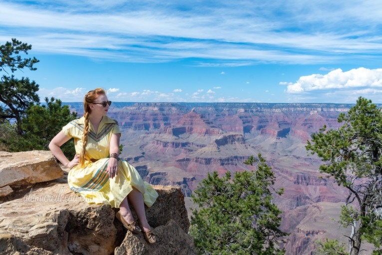 Myself sitting on a rock in front of the Grand Canyon, wearing a pale yellow dress with copper and teal blue rick-rack trim, and a tan beaded belt, my hair in one long braid.