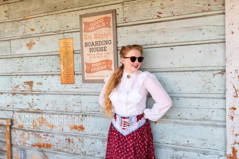 Myself standing against an old west building wearing a long sleeve, white blouse with ruffles down the center, and a cranberry floral print skirt with lace trim.