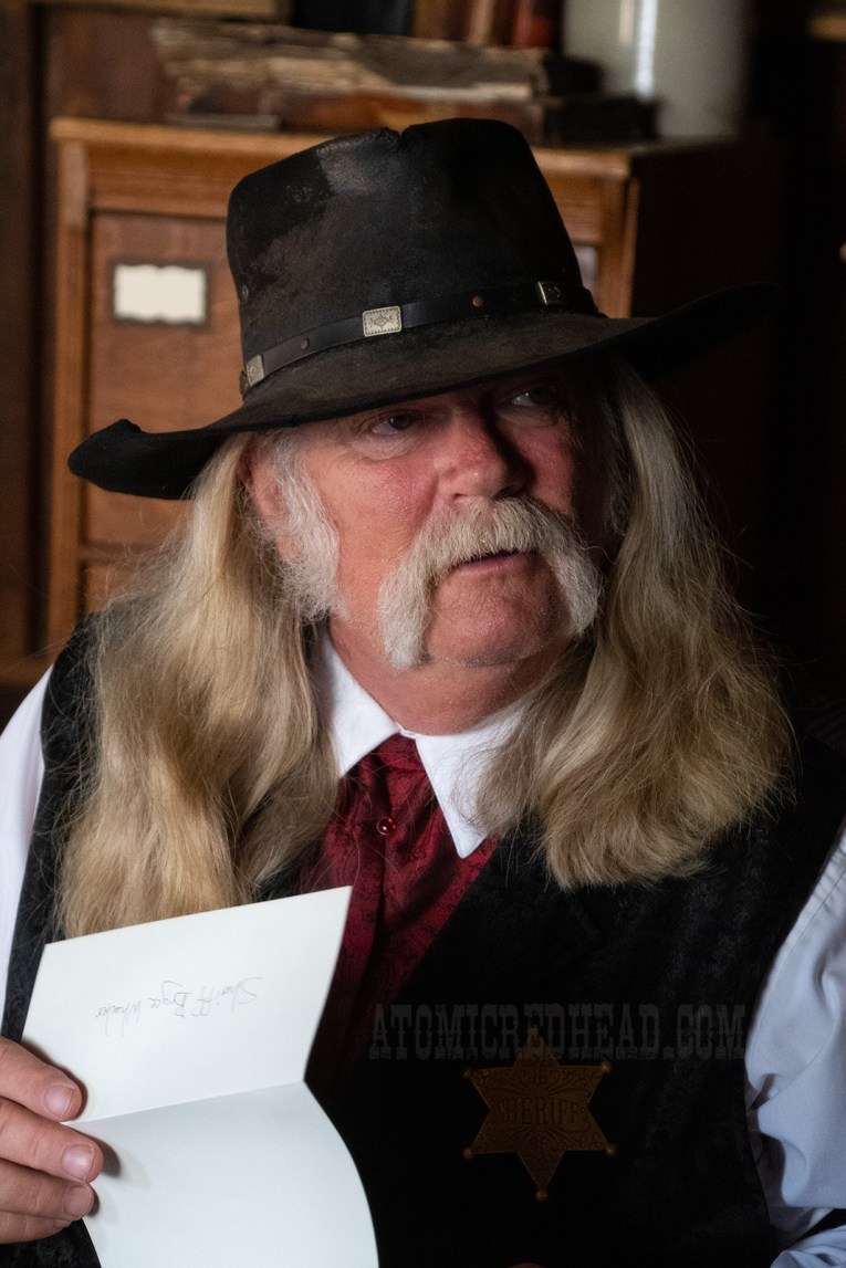 Sheriff Wheeler, the town's law, reads a letter. He wears a black cowboy hat, white shirt, with black brocade vest, and red tie. He has long grey hair and a bushy grey moustache.