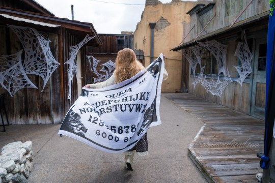 Myself, walking away from the camera with the black and white Ouija board shawl billowing out behind me.