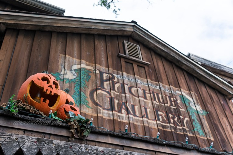 "The wooden building for the ""Pitcher Gallery"" features jack-o-lanterns on the edge of its eve."