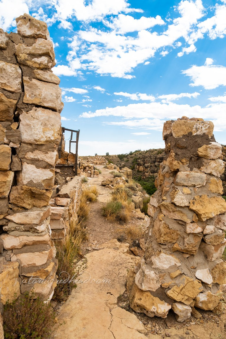 Crumbling walls along a path at the edge of the canyon.