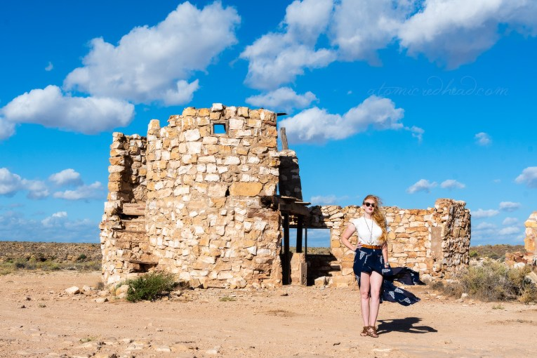 Myself, wearing a white peasant top, and a long, navy skirt with cattle skulls printed on it, and a necklace featuring a cattle skull standing next to one of the rock work ruins.