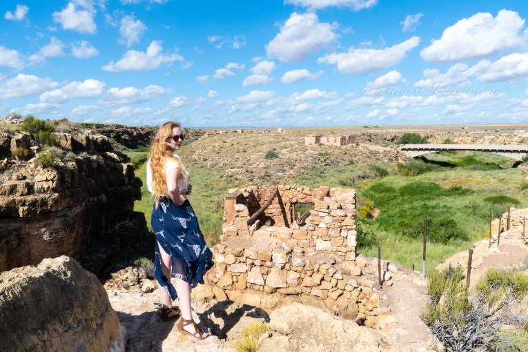 Myself, wearing a white peasant top, and a long, navy skirt with cattle skulls printed on it, and a necklace featuring a cattle skull standing next to one of the rock work ruins that overlooks the canyon.