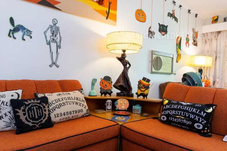 A warm wood corner table sits between our two couches. Spirit board pillows sit on the couch. A dapper jack-o-lantern and a dapper cat paper Halloween decorations sit on either side of a lamp.