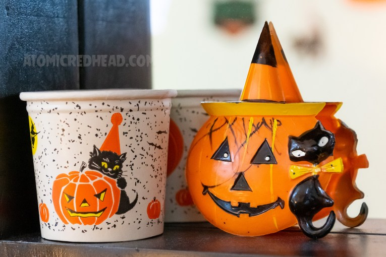A paper cup with a jack-o-lantern and a black cat wearing an orange party hat. Next to it a plastic jack-o-lantern with a witch's hat, and a black cat.