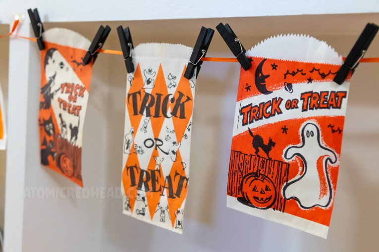 Close up of several trick or treat bags, which include images of ghosts, black cats, moons, stars, and jack-o-lanterns.