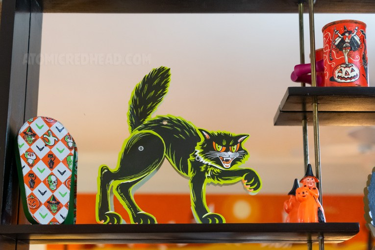 Close-up of a paper black cat and a noise maker with a diamond pattern that also features images of skulls, witches, cats, and pumpkins.