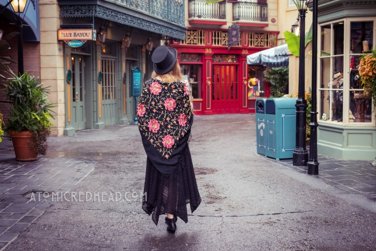 Myself, walking down one of the streets of New Orleans Square, a black top hat on my head, and a black shawl with pink embroidered flowers.