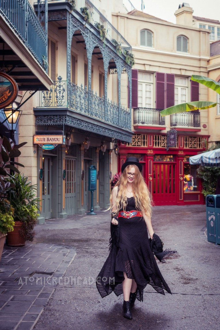 Myself below the green curling wrought iron balconies of New Orleans Square. Wearing a black top hat, black lace dress, with red, blue, and gold belt featuring an eagle, and short black boots.