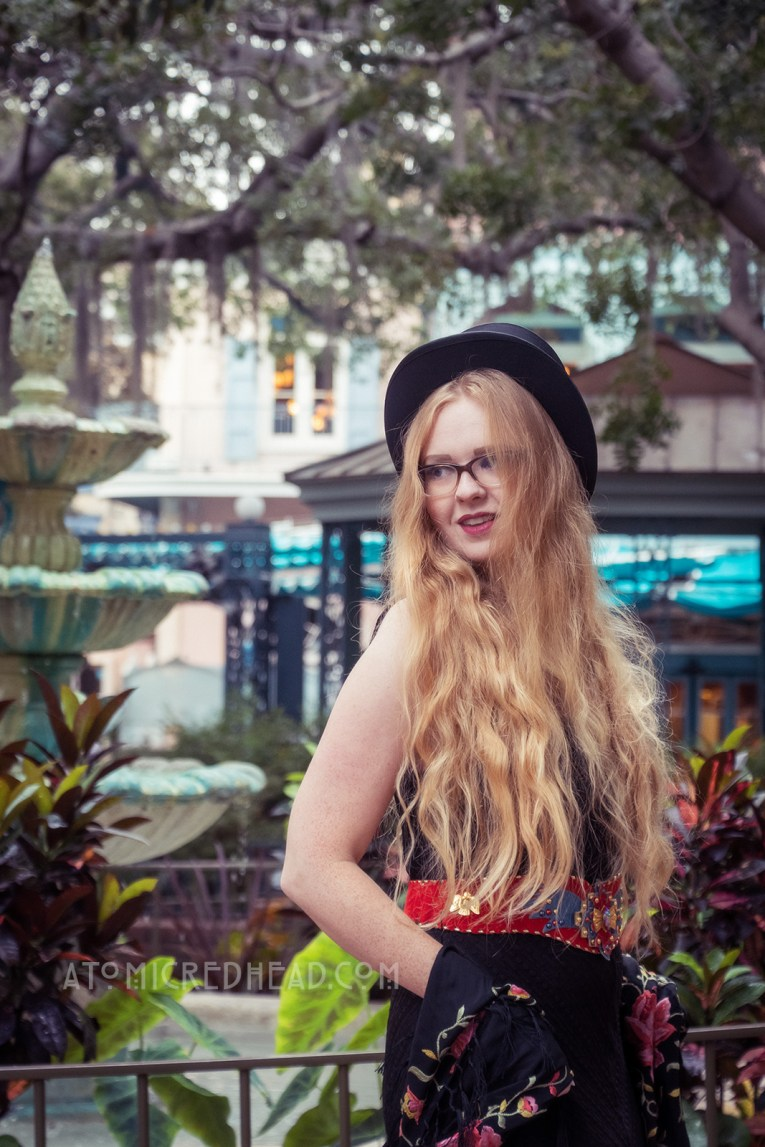 Myself standing near a fountain under trees of Spanish moss, wearing a black top hat, black lace dress, with red, blue, and gold belt featuring an eagle, a black shawl with pink flowers embroidered on it around my shoulders, and short black boots.