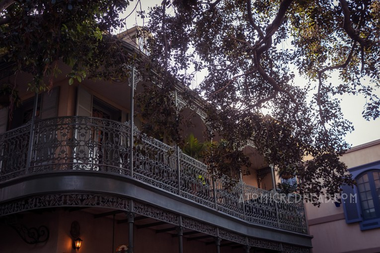 A dark green wrought iron balcony peeks from behind a tree.