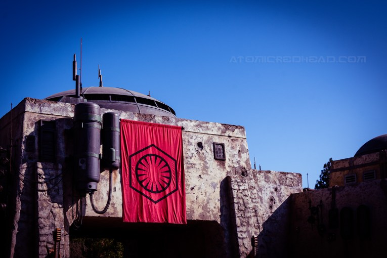 A red and black First Order banner hangs from a grey building with a domed roof.