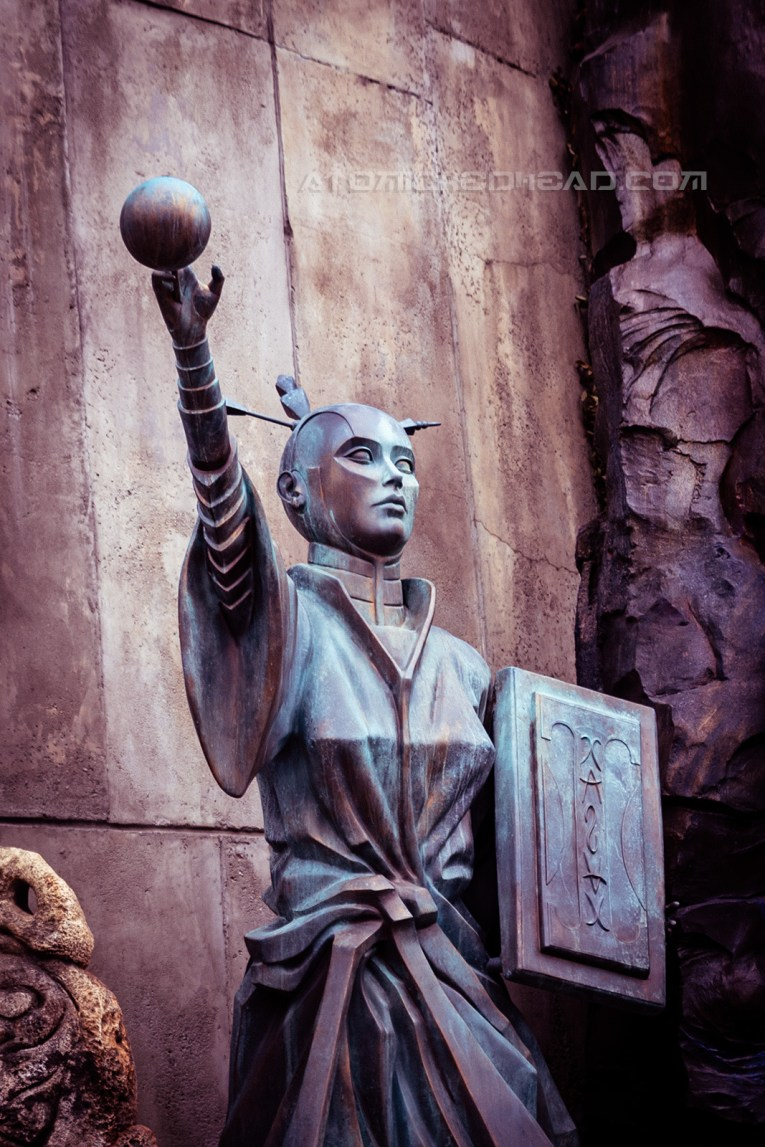 A statue of an etherial woman in a robe with her hand out stretched toward an orb like object. A book is held in her other hand.