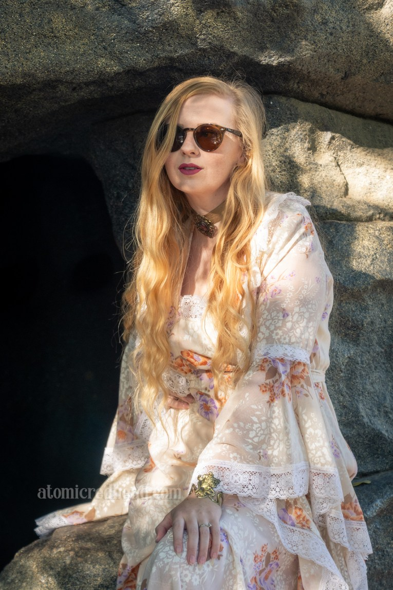 Myself, standing in front of a cave opening, wearing a full length pale tan yellow dress, with a tan and purple floral print. The sleeves are a long bell sleeve edged in lace.