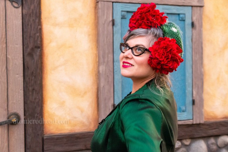 My friend Danielle wears a green ensemble of a swing dress and matching bolero topped with a small green hat and red flowers.