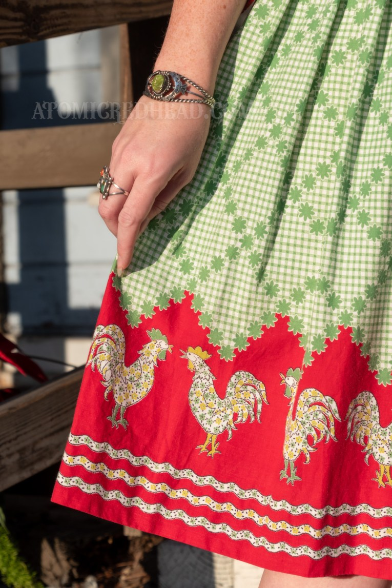 Close-up of my skirt, which is green and white check until the hem which is red and features green and yellow chickens.