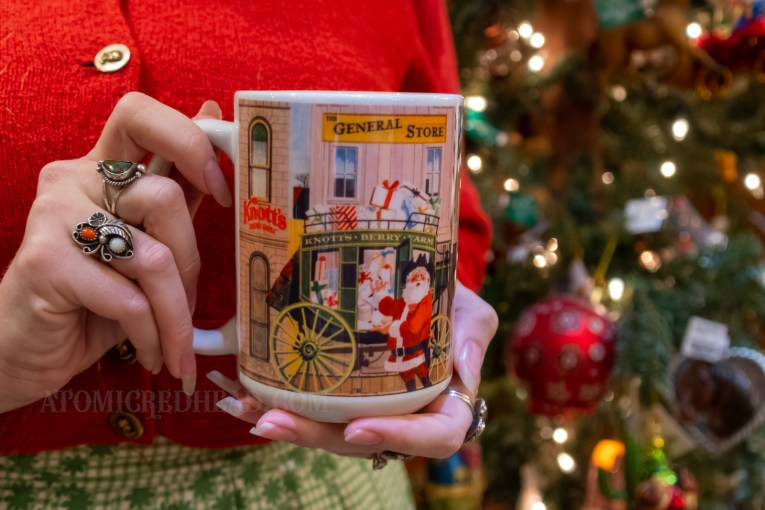 Myself holding a mug featuring an image of Santa in a cowboy hat in front of a stagecoach loaded down with presents.