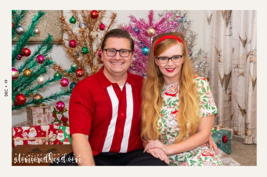 Patrick and I sit in front of our forest of aluminum Christmas trees. Patrick wears a red, black, and white button up sweater, and black pants. I wear a white dress with a design of Santas and holly.