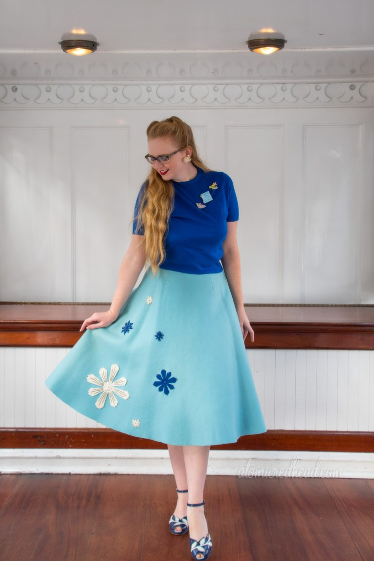 Myself, standing aboard the Mark Twain, a white paddle wheeler, wearing a bright blue sweater, and a light blue skirt with white and dark blue snowflakes sewn on.
