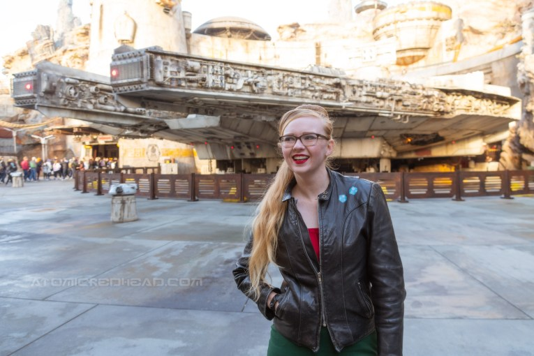Myself, standing in front of the Millennium Falcon, wearing a black leather jacket with a pair of blue sabacc dice painted on the upper left.