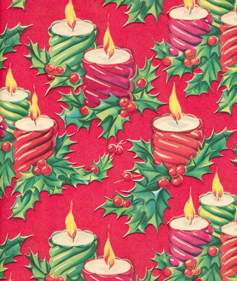 Red, green, and pink candles sit in holly leaves against a red background