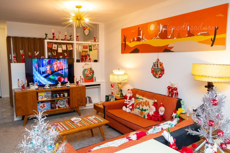 Overall view of our living room. A desert painting hangs above one couch, the other coach faces the TV which plays a vintage Chip and Dale cartoon. Vintage stuff Santas sit on the couches.